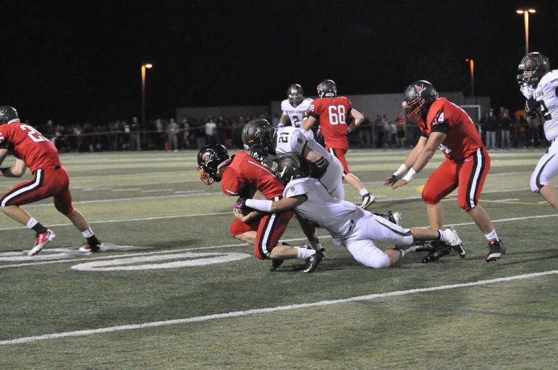 by: TRACIE KRELLWITZ - Gavin Andersen and Ryan Anderson combine to make a tackle in last week's game against Clackamas.