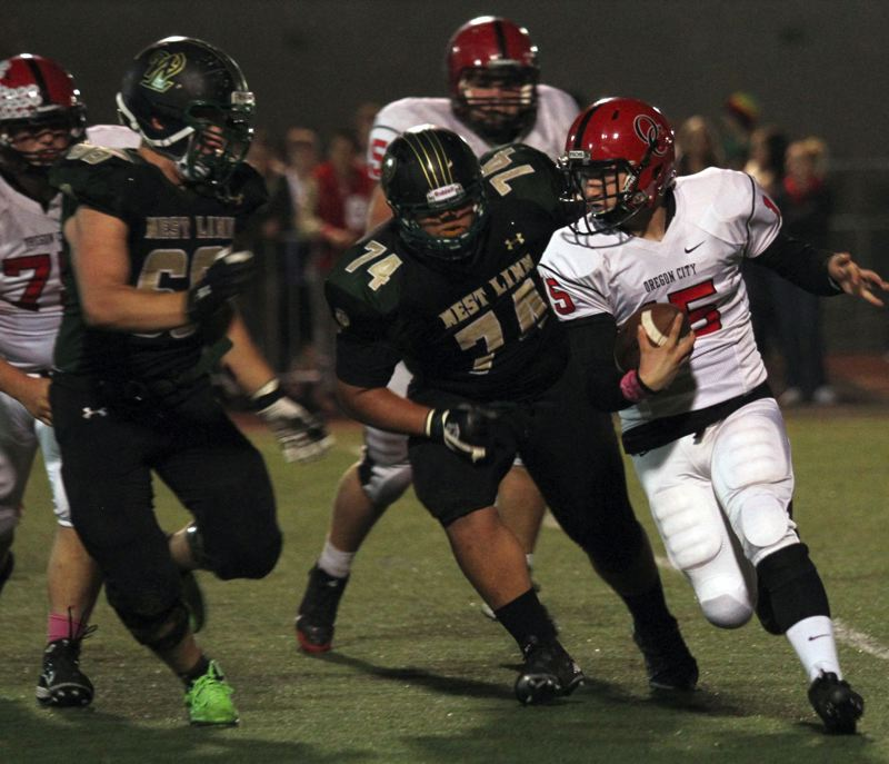 by: JONATHAN HOUSE - Oregon City quarterback Jon Hall (5) played a major role last week, as the Pioneers defeated their cross-town rivals for the first time since 2002. Oregon City also won at the jayvee and freshmen levels.