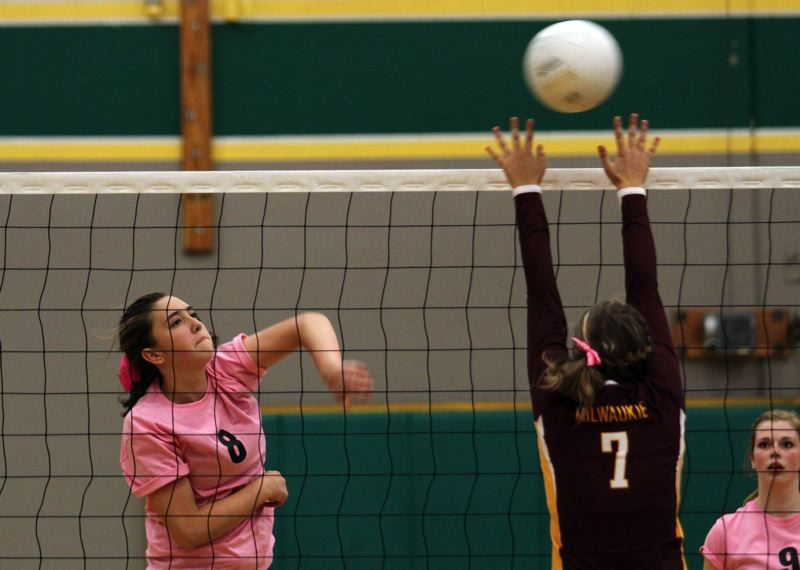 by: JONATHAN HOUSE - Putnam senior Amanda Burge (8) powers the ball past Milwaukie middle blocker Emily Downs in last weeks match with the Mustangs. The Kingsmen defeated the Mustangs 25-10, 25-16, 25-15, avenging an earlier loss.