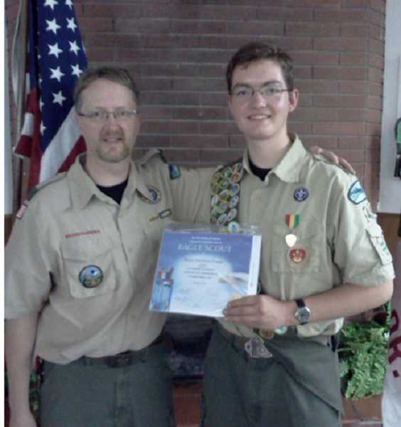 by: SUBMITTED PHOTO  - Scout Master Eric Carter, left, presents Henry Frame with a certificate verifying he has earned the rank of Eagle Scout.