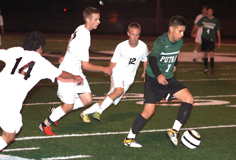 by: KRISTOPHER ANDERSON - From left to right, Sandy players Alexis Marin, Wyatt Edwards and Anthony Krening chase a Putnam forward during a 3-1 loss last Thursday.