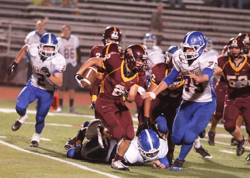 by: CHASE ALLGOOD - Forest Grove junior Cody Smith tries to outrun Newberg's Bryce Schubert (79) during Thursday's Pacific Conference game. The Vikings won 21-14 for their first victory of the season.