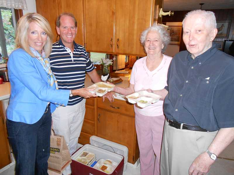 by: CLIFF NEWELL - Friendship and food are delivered by the Lake Oswego Meals-On-Wheels program. From left are drivers Lorri and Mike Kehoe and recipients Betty and Art Sorenson.