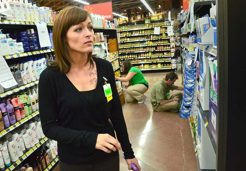 by: VERN UYETAKE - Ashley Knipe, manager of the new Walmart neighborhood market off Boones Ferry Road, oversees the chaos as the store comes together ahead of its opening, planned for Wednesday.