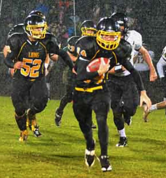by: JOHN BREWINGTON - St. Helens' quarterback Gage Bumgardner (14 below right) picked up some yardage with an escort during the rain on Friday night.