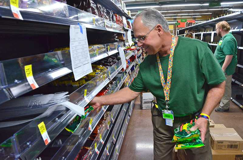 by: VERN UYETAKE - Gregg Leonetti of Lake Oswego stocks shelves at the new neighborhood market in the Lake Grove area.
