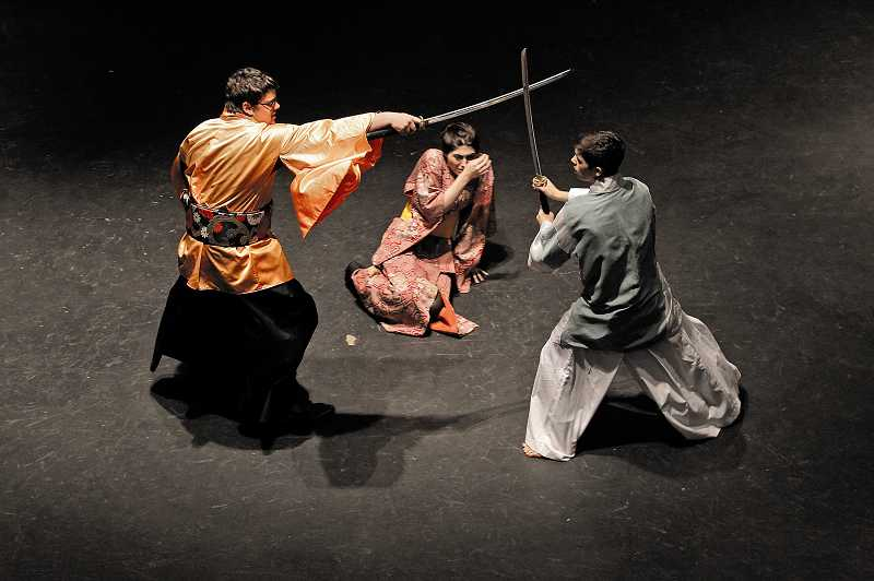 by: JAIME VALDEZ - Tualatin High School senior Kent Edgerton, left, as the bandit, battles sophomore Braedon Kwiecien, as the samurai, during Tualatin High School's production of 'Roshomon' as senior Jamie Perry looks on in the role of the samurais wife. The production opens Nov. 7 in the Tualatin High School Auditorium.