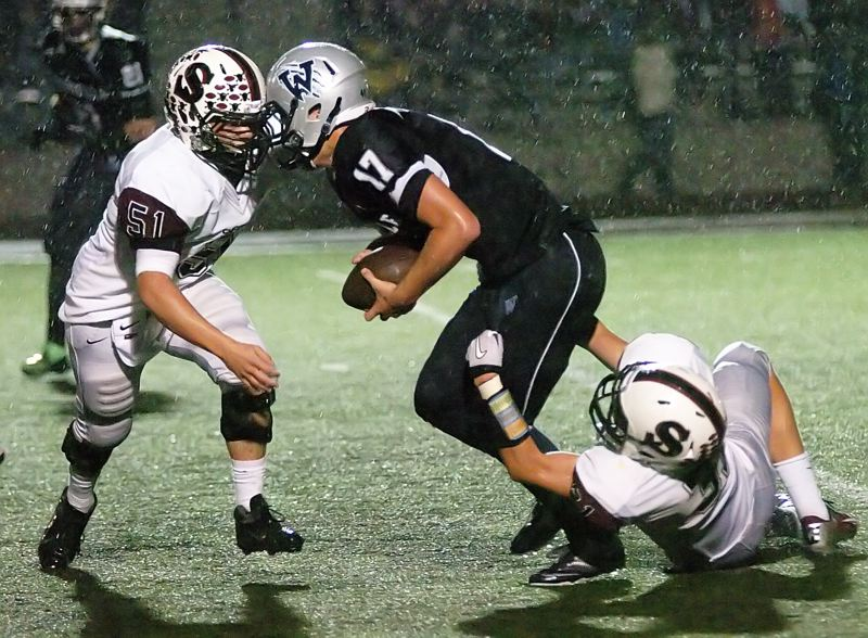by: DAN BROOD - SACK ATTACK -- Sherwood High School senior Nick Rowlands (51) and sophomore Zak Taylor team up to bring down Wilsonville senior quarterback Nick Highberger in Friday's game.