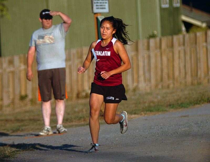 by: DAN BROOD - TURNING THE CORNER -- Tualatin High School Christine Ho picks up the pace during last week's dual meet against Forest Grove.