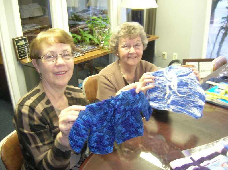 by: REVIEW PHOTO: CLIFF NEWELL - Nancy White, left, and Bev Whitehead display the baby garments the church has prepared for UMCOR.