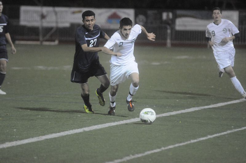 by: MATTHEW SHERMAN - Ryan Barber looks to beat a Canby defender to the ball in last week's victory by the Lions.
