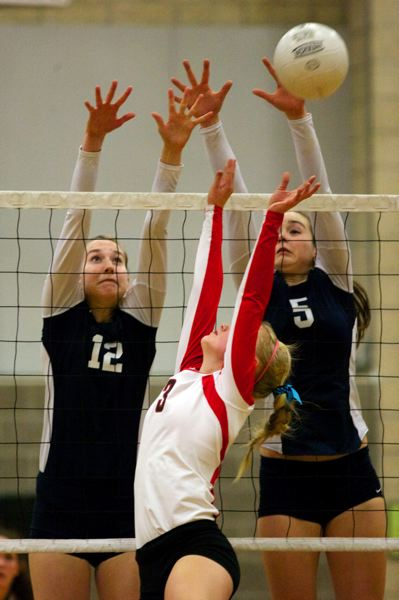 by: JAIME VALDEZ - Lake Oswego's Erika Treske, left, and Heather Pippus go up for a block in Tuesday's match against Clackamas. The Cavaliers won in straight sets to clinch at least a share of the league title.