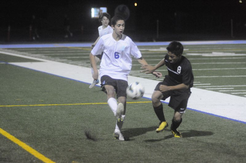 by: MATTHEW SHERMAN - Lakeridge's Eleonso Cristobal makes a pass against an Oregon City defender during Tuesday's game against the Pioneers. Lakeridge scored first but gave up a pair of goals in the second half in a 2-1 defeat.