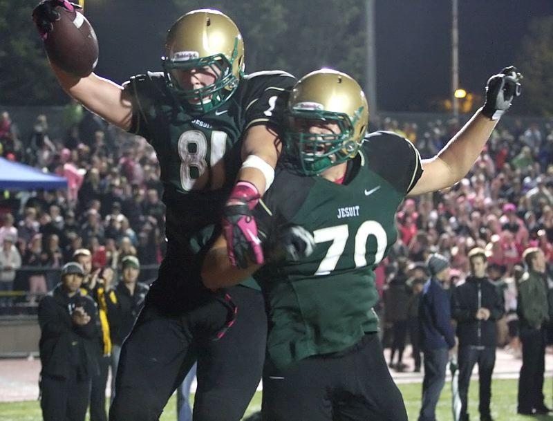 by: MILES VANCE - SCORE AND SOAR - Jesuit tight end Henry Mondeaux (left) and lineman Ryan Brown celebrate one of Mondeaux's two touchdowns in his teams 56-13 Metro League home win over Aloha on Friday.