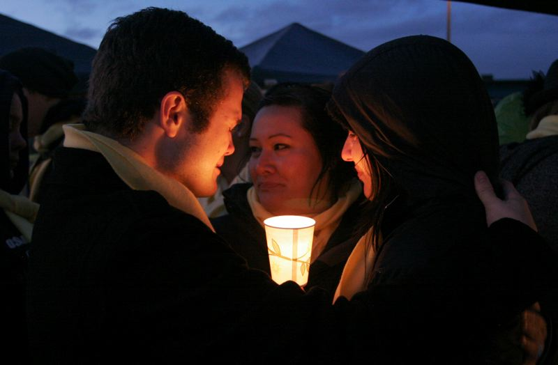 by: OUTLOOK PHOTO/ JIM CLARK - Starbucks workers comfort one another at the Saturday night candlelight vigil for Whitney Heichel.