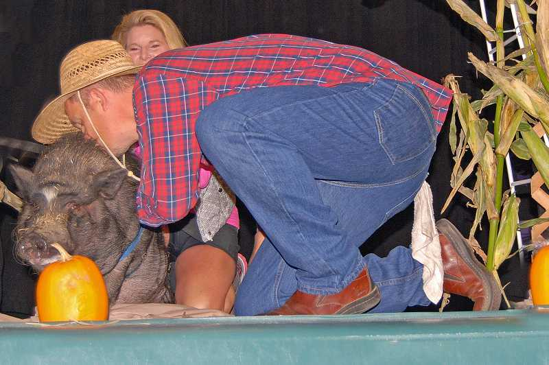 by: SUBMITTED PHOTO  - Because the school raised more than $5,000 during its fun run, Principal Peter McDougal kissed a pig during the morning assembly in front of the entire school.