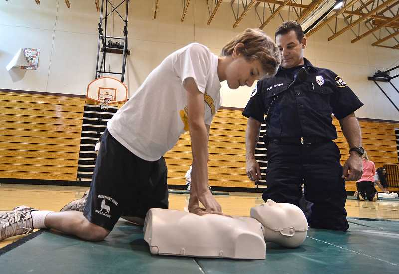 by: TIDINGS PHOTO: VERN UYETAKE - Seventh-grader Dylan Jahnson and TVF&R firefighter Mike Thorne practice hands-only CPR at Rosemont Ridge Middle School.