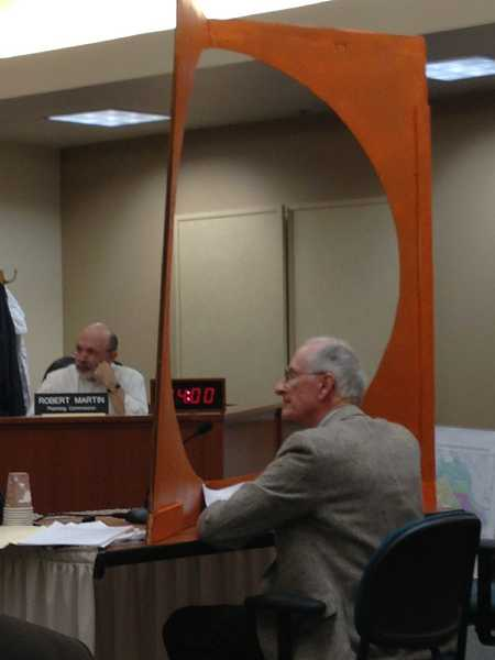 by: LORI HALL - Steve Hopkins testifies before the planning commission behind a cutout of a 4-foot-diameter circle representing the proposed pipeline.