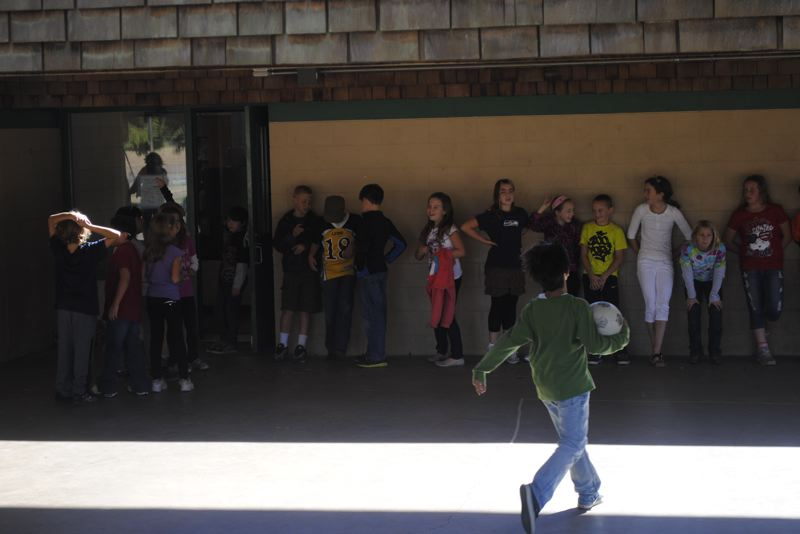 by: STOVER E. HARGER III - Students run to line up after recess at Sauvie Island Academy.
