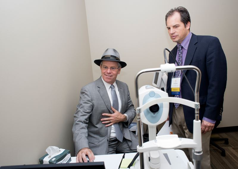 by: NEWS-TIMES PHOTO: CHASE ALLGOOD - Kenneth W. Eakland, Associate Dean for Clinical Programs at the Pacific University College of Optometry, shows Virginia Garcia CEO Gil Munoz new optometry equipment at the vision center in the new Cornelius Wellness Center.