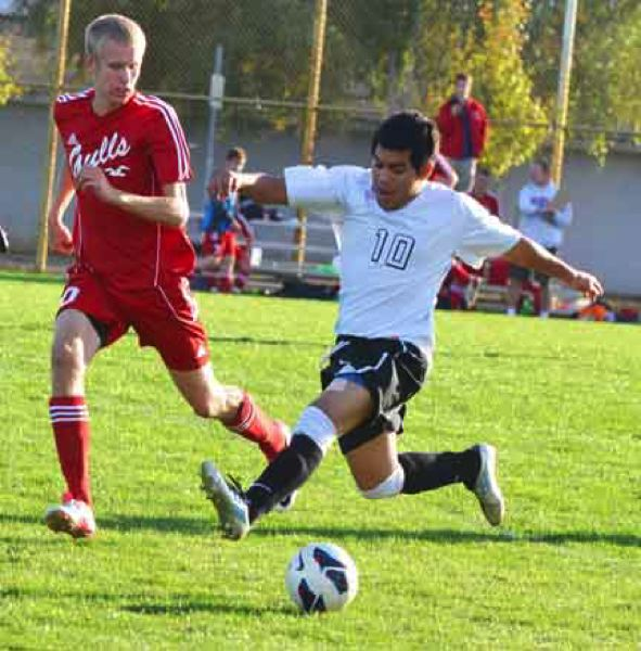 by: JOHN BREWINGTON - Scappoose's Jesus Martinez brings the ball down the field on the fly with Soren Johannsen of Seaside in hot pursuit. The Indians lost to the Gulls, 2-1.