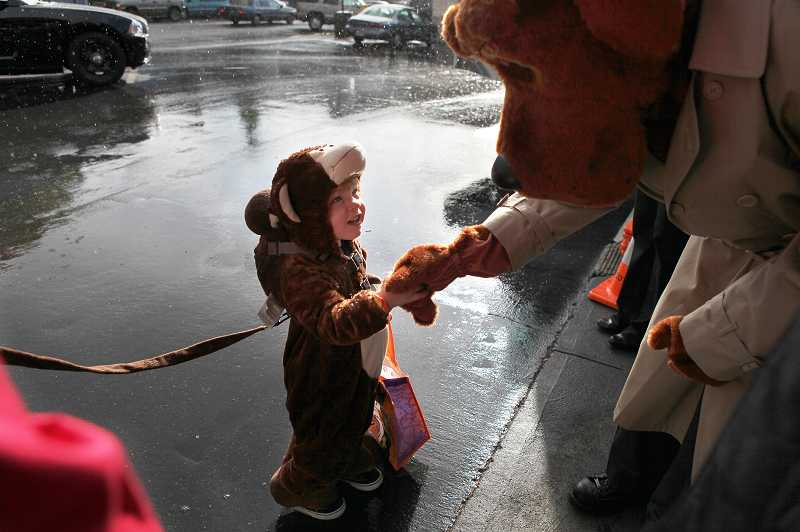 by: JAIME VALDEZ - A monkey gets from candy from McGruff the Crime Dog, during Tigard Main Streets annual Trick of Treat celebration. The annual event begins at 3 p.m., Halloween day.