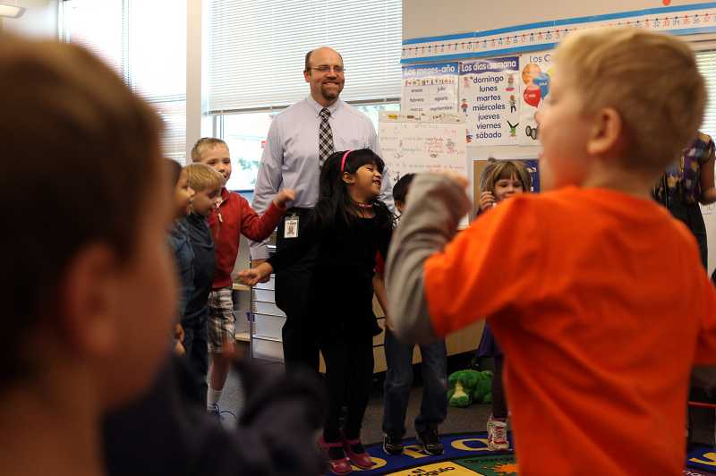 by: JAIME VALDEZ - Metzger Elementary School principal Craig Sproles watches as a Spanish-language kindergarten class dances and sings the days of the week in Spanish. Sproles has confidence that the new program will help increase performance of Spanish-language students.