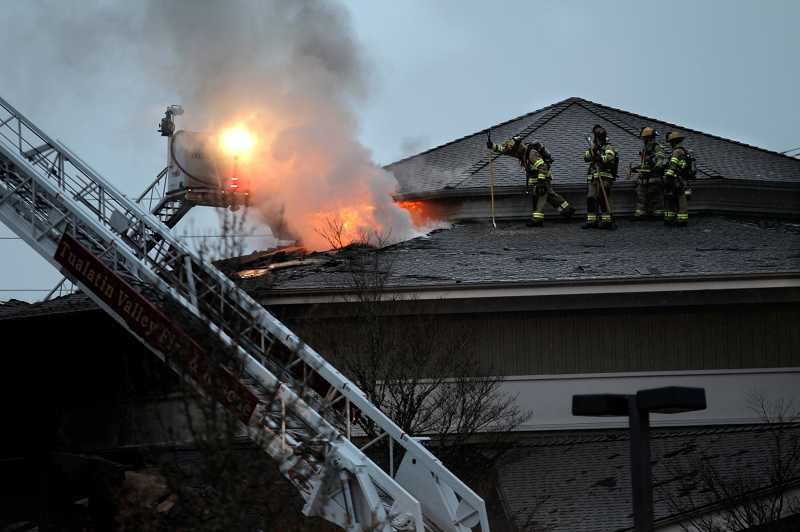 by: JAIME VALDEZ - TVF&R firefighters work on extinguishing a March 19 fire at the Living Savior Lutheran Church in Tualatin.