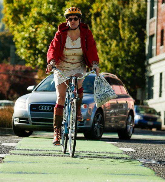 by: TRIBUNE PHOTO: CHRISTOPHER ONSTOTT - PSU student Stephen Bridges pedals up the cycle track on Southwest Broadway. Bike advocates say more such protected bike lanes are needed.