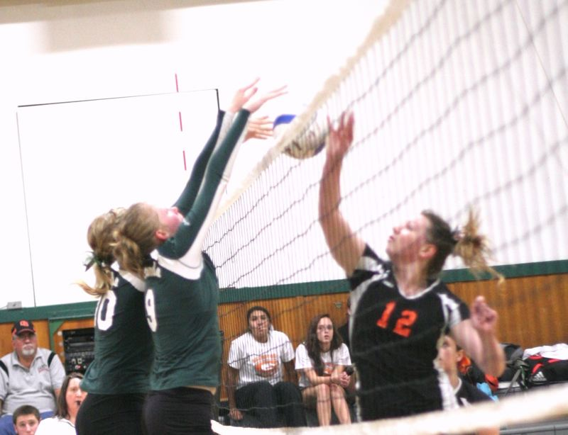 by: PHOTOS BY LOREN NIBBE - Sam Hammons and Rachel Lowe go up for the block, as both girls continue to dominate opponents this season.