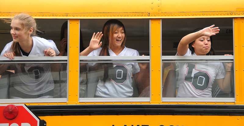 by: REVIEW PHOTOS: VERN UYETAKE - Picture 1 - From left, cheerleaders Helene Barkhuizen, Erin Oh and Claudia Herrera start the cheering on the bus on their way to the parade.