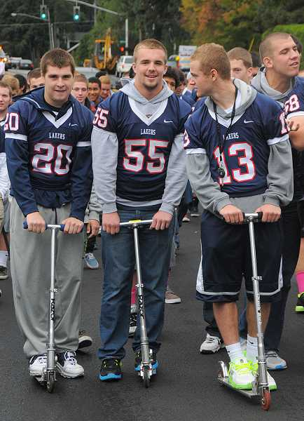 Members of the football team scootered down A Avenue during the traditional homecoming parade. Pictured are, from left, Neil Wagner, Austin Faunce and Chad Walker.