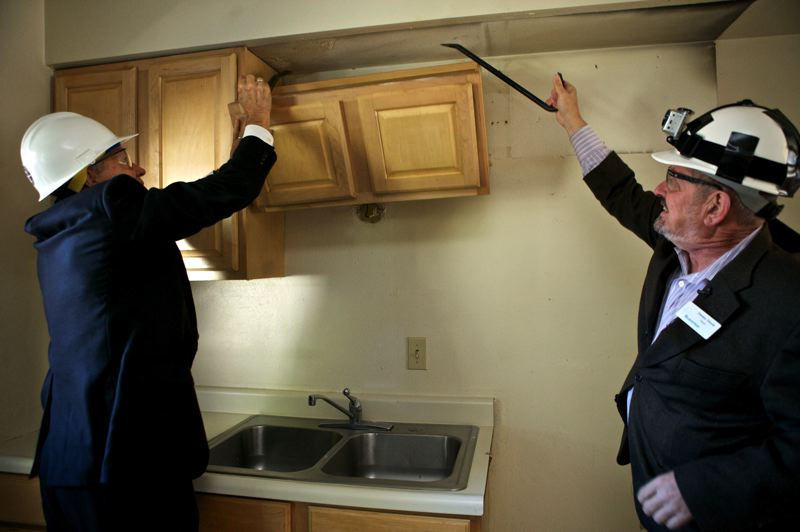 by: JAIME VALDEZ - Boys & Girls Aid President and CEO Michael Balter and Beaverton City Mayor Dennis Doyle demolish kitchen cabinets at an apartment that is being renovated for a Transitional Living Program. The program will serve Washington County youth ages 16 to 21 who are facing homelessness or unstable housing.