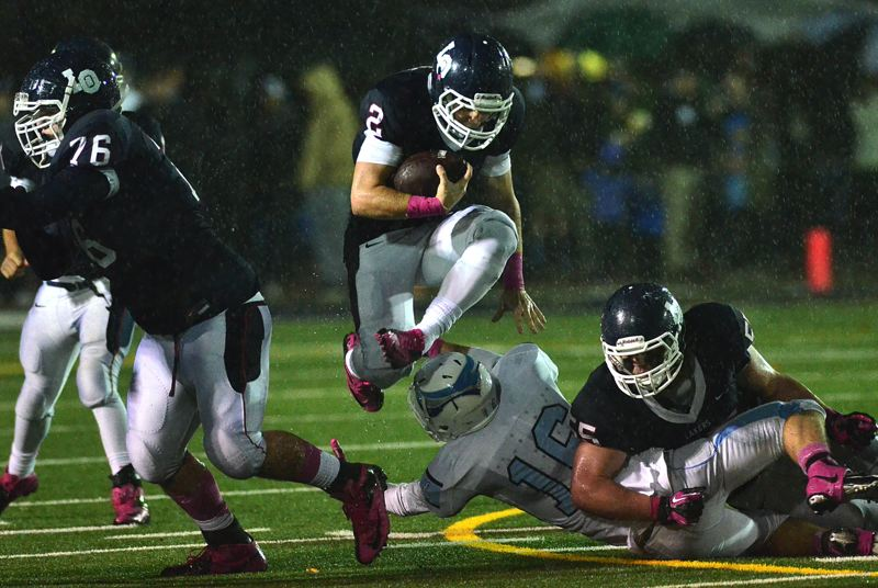 by: VERN UYETAKE - Lake Oswego's J.B. Holmes makes a run during a rainy first half of last week's Civil War game.