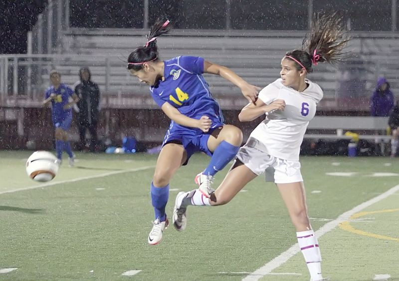 by: MILES VANCE - GOING HARD - Aloha junior Laura Nguyen (left) heads the ball away from Sunset sophomore Crystal Kyanko during the Warriors' 0-0 tie with the Apollos in Metro League action at Sunset High School on Oct. 18.