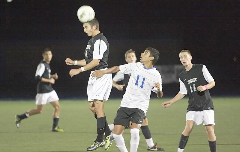 by: MILES VANCE - HEAD OF THE CLASS - Jesuit senior Brian DeGrandmont makes a header while defended by Aloha