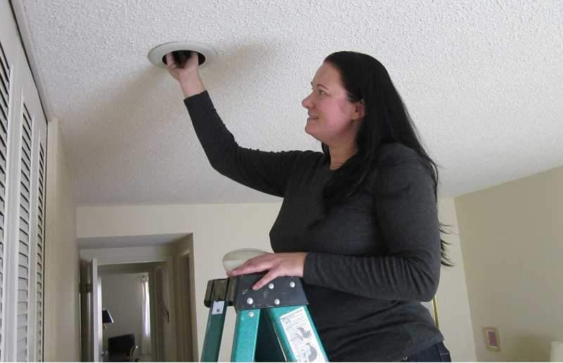 by: BARBARA SHERMAN - ALL IN A DAYS WORK - Desiree Perkins, a weatherization technician with Good Energy Retrofit, replaces a floodlight with a CFL floodlight in a Summerfield home for sale.