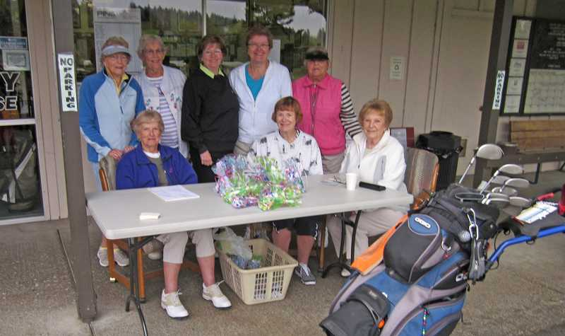 by: BARBARA SHERMAN - READY TO EARN MONEY AND PLAY - Members of the King City Womens Golf Clubs fundraising committee stand behind other members checking in players before the start of weekly play Sept. 26.