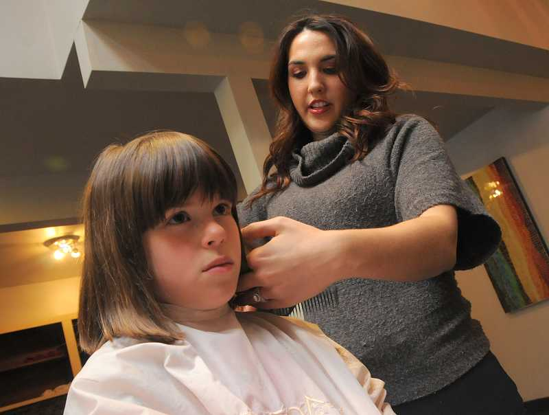 by: TIDINGS PHOTO: VERN UYETAKE - GiGi Salon in West Linn gave back to the Bolton community by offering free haircuts for children on Oct. 23. Stylist Morgan O'Neil at GiGi Salon gives Delaney Lallum a free haircut.