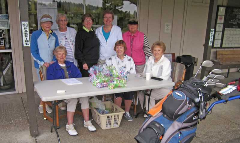 by: BARBARA SHERMAN - READY TO EARN MONEY AND PLAY - Members of the King City Women's Golf Club's fundraising committee stand behind other members checking in players before the start of weekly play Sept. 26.