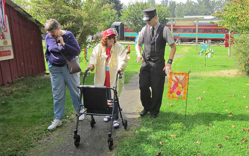 by: BARBARA SHERMAN - ALL ABOARD! - Pat Carter (left) and Molly Madigan talk to the Mount Hood Railroad conductor while walking in Parkdale.