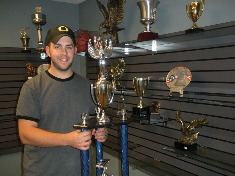 by: POST PHOTO: JIM HART - POST PHOTO: JIM HART Grant Baker stands in the middle of some of the awards and trophies he has created. Baker has changed the name of his Sandy business; has moved to a newly remodeled storefront; and is expanding his services and products.