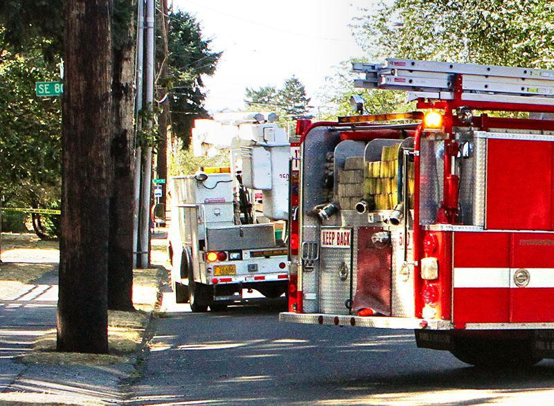 by: DAVID F. ASHTON - Portland Fire & Rescue Engine 11 blocks S.E. Holgate Boulevard, after a power line falls across the street. Behind the fire engine, crews arrive to start repair on the downed power line.