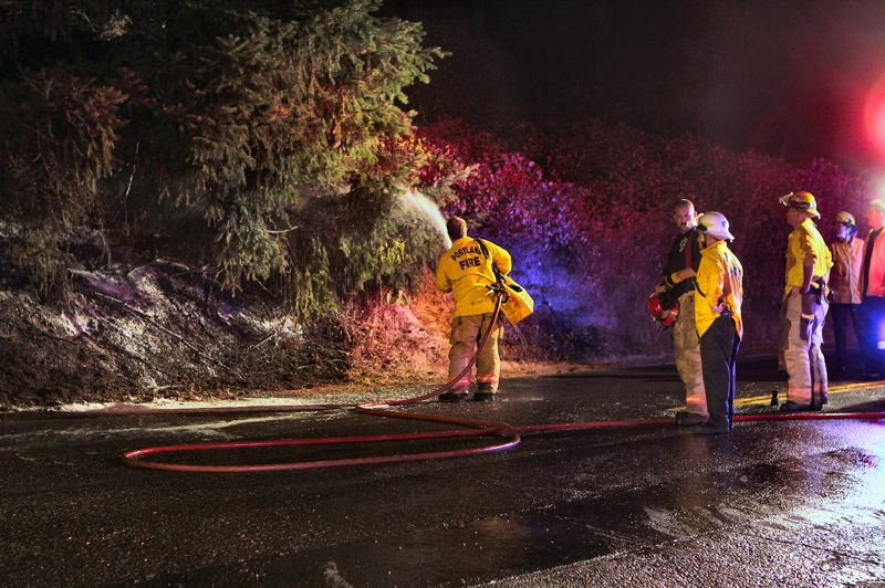 by: DAVID F. ASHTON - After the fire was extinguished, the crew looked on as a firefighter sprayed tinder-dry brush and grass with flame-retardant foam.