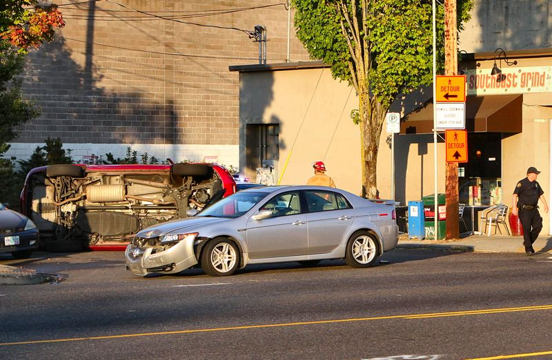 by: DAVID F. ASHTON - Westbound S.E. Powell Boulevard traffic comes to a stop, while first-responders check for injured people at this accident scene.