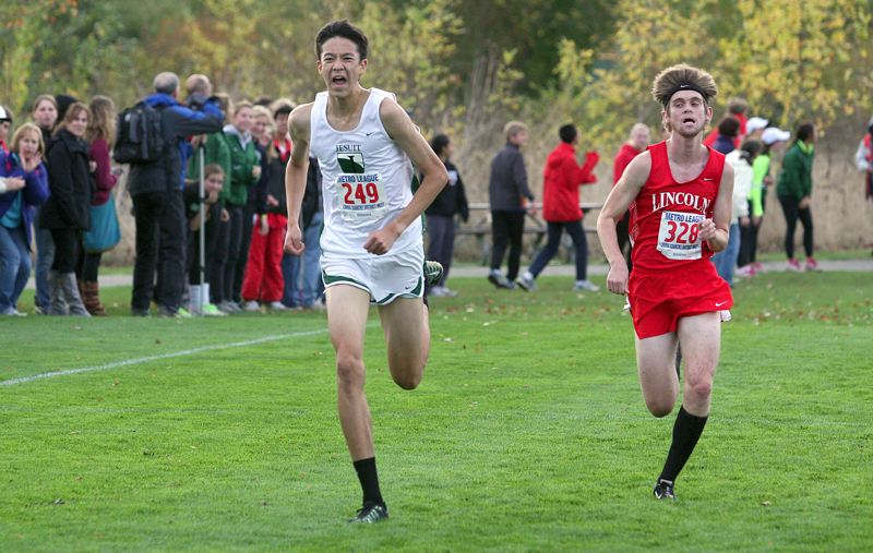 by: MILES VANCE - DUEL TO THE FINISH - Jesuits Josh Sealand (left) accelerates past Lincolns Tanner Smith en route to a runner-up finish in the Metro League District meet at Tualatin Hills on Oct. 25.