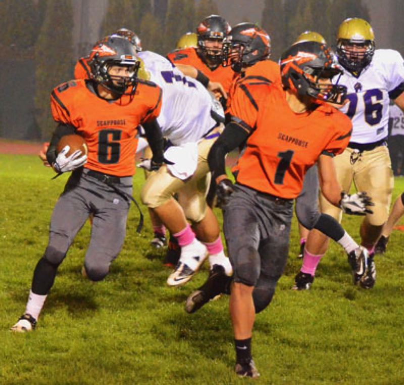by: JOHN BREWINGTON - Scappoose's Paul Revis (6) follows Carson Davison's (1) lead during Friday's game. Revis was a big part of the Tribe's 57-6 win.