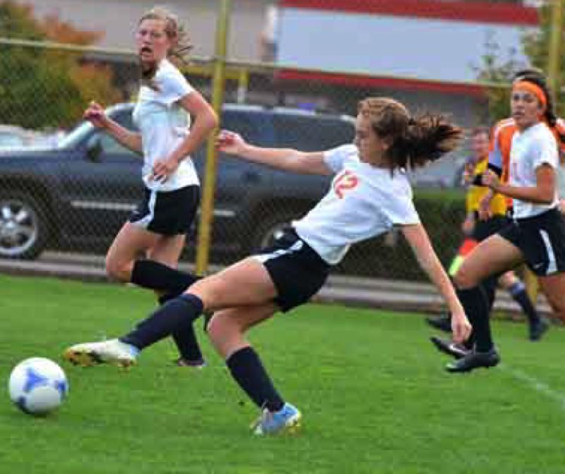 by: JOHN BREWINGTON - Scappoose's Natalie Muth takes a weak shot at goal off the tip of her foot during last week's 8-0  win over Yamhill-Carlton. Scappoose has sewn up the Cowapa League and No. 2 state playoff berth.