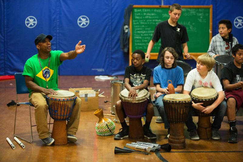 by: TRIBUNE PHOTO: CHRISTOPHER ONSTOTT - Chuk Barber, African-Brazilian drum instructor, drums alongside his middle school students at Faubion.
