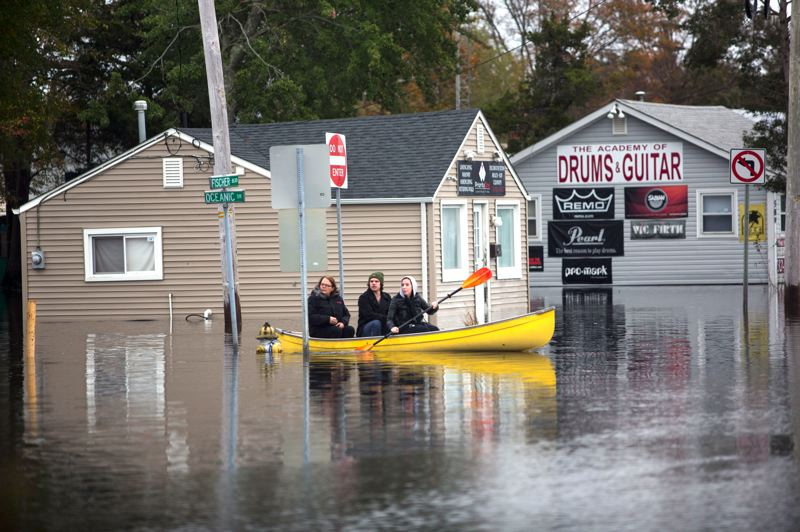by: CONTRIBUTED PHOTO: LES STONE/AMERICAN RED CROSS - Rescue personnel used boats and even front-end loaders to reach residents stranded by the Atlantic tidal surge compounded by the heavy rain and winds of Hurricane Sandy earlier this week. Pictured here are residents of Toms River, N.J., using a boat to navigate flooded streets.